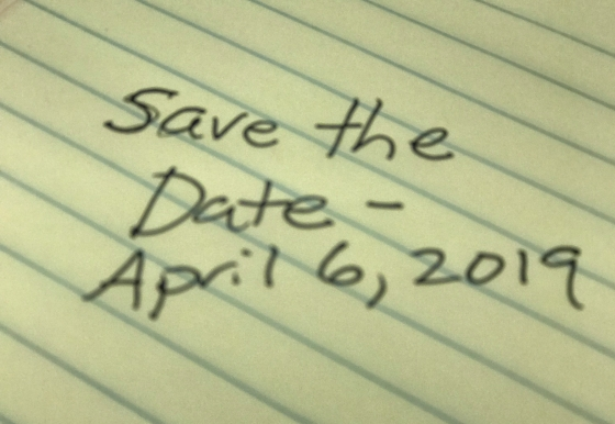 Save the Date - April 6, 2019 written on yellow legal pad in soft focus