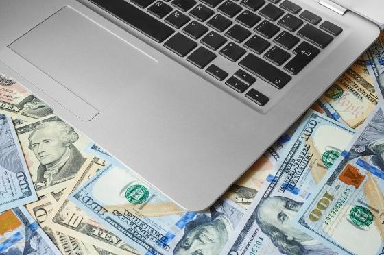 A laptop gauchely setting on money.