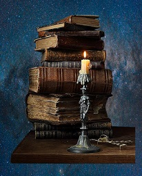 A lit candle in front of some books