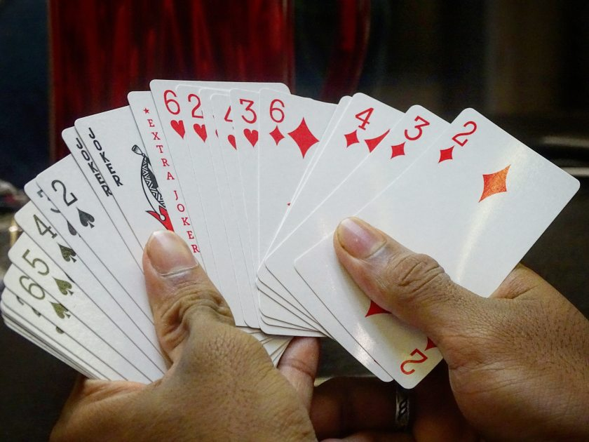 Person holding cards including 3 jokers